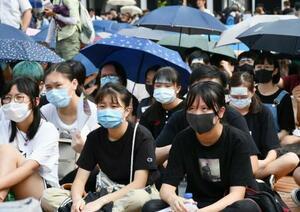 香港中心部で開かれた集会に参加した女子生徒ら=22日(共同)