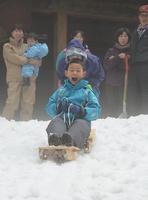 廃材と竹で作ったそりで斜面を滑り降りる児童=13日、福井県南越前町二ツ屋