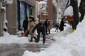 歩道に積もった雪を除雪する人たち=25日午前8時ごろ、福井市大手3丁目