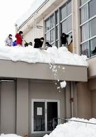 雪の影響で体育館の窓が割れ、応急処置として木の板をあてがうために窓付近の雪かきをする教員たち=1月12日、福井県福井市順化小学校