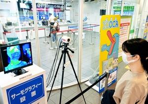 設置されたサーモグラフィーで体温を測定する駅利用者=7月16日、福井県福井市のJR福井駅