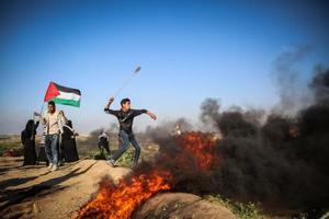 22日、パレスチナ自治区ガザでイスラエル軍に抵抗するパレスチナ人ら(ゲッティ=共同)