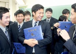 卒業証書を手にクラスメートと談笑する牧丈一郎投手(中央)=1日、福井市の啓新高