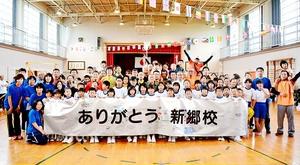 新郷小の思い出を書き込んだ横断幕を手にする体育祭に参加した児童や新郷体協関係者ら=9月19日、福井県あわら市の同校