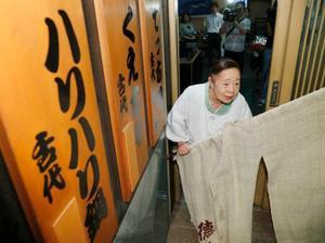 クジラ料理店「徳家」が営業を終え、のれんを外すおかみの大西睦子さん=25日夜、大阪市
