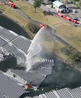 山倉ダムに設置された太陽光パネルが出火し続く消火活動=9日午後、千葉県市原市(共同通信社ヘリから)