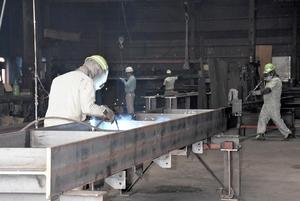 外国人技能実習生が黙々と仕事をこなす鉄工所。経営者は「求人しても日本人は来ない」と嘆く=福井県内
