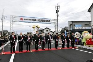 テープカットし岡山松陵線開通を祝う出席者ら=12月14日、福井県敦賀市金山