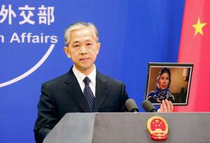 中国新疆ウイグル自治区での性被害を証言した女性の写真を手に「うそつき」と非難する外務省の汪文斌副報道局長=23日、北京(共同)