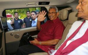 17日、スリランカ・コロンボで、報道陣に手を振り自宅を出発するラジャパクサ氏(AP=共同)