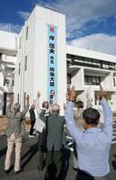 山口県田布施町役場で、岸信夫氏の防衛相就任を祝う垂れ幕を掲げ喜ぶ人たち=25日午後