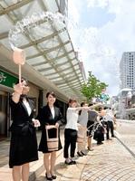 暑さを和らげようと打ち水をする商店街の店員ら=7月23日、福井県福井市中央1丁目