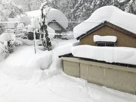雪に埋もれる住宅=13日午後2時25分ごろ、福井県大野市朝日