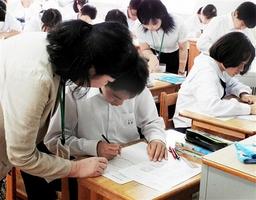 教諭のアドバイスを受け、新聞記事の要約に取り組む生徒たち=29日、福井県越前市武生三中
