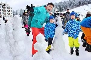 雪だるまを作り、サバンナの八木真澄さん(中央)と喜ぶ地元の子どもたち=1月27日、福井県勝山市のスキージャム勝山