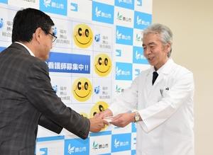 兜正則院長(右)に500万円の目録を手渡す山岸正裕市長=6月27日、福井勝山総合病院