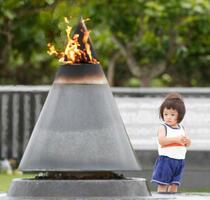 「慰霊の日」を前に平和祈念公園を訪れ、「平和の火」を見つめる子ども=22日午後、沖縄県糸満市