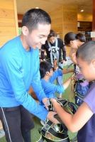 メガジップライン体験者の補助をする右馬さん(左)。「いろんな人と交流ができるのが楽しい」と話す=福井県池田町のツリーピクニックアドベンチャーいけだ