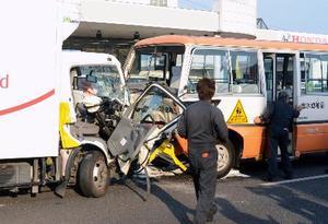 国道で衝突したトラックと送迎バス=22日午後5時26分、熊本市中央区