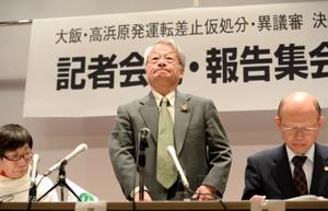 厳しい表情で記者会見の席につく弁護団共同代表の河合弘之弁護士(中央)ら=24日、福井県国際交流会館