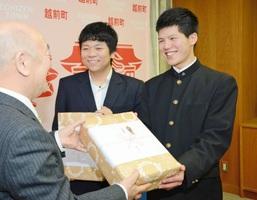 福井県越前町の内藤俊三町長(左)から記念品を受け取る石川さん(右)と古田さん=1日、越前町役場