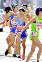 走り出す女子美方の2区橋本はなえ(中央)。1区吉村奈々(中央奥)から37位でたすきを受け取る=京都市内の第1中継所