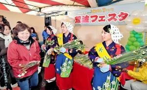水仙まつりが開幕し、水仙娘から笑顔で水仙をプレゼントされる来場者=17日、福井県南越前町河野の河野シーサイドパーク