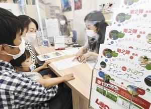 旅行会社で宿泊を申し込む親子(左)=7月11日、福井県坂井市のハッピートラベル春江本店