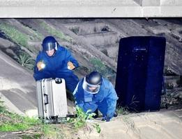 橋の下に置かれたスーツケースを調べる爆発物処理班=9月22日午後7時20分ごろ、福井県福井市上北野2丁目
