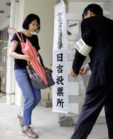 福岡県久留米市の投票所に向かう有権者。大雨の影響で投票開始時刻が2時間遅れた=21日午後