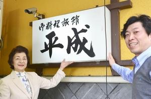 愛着ある旅館の看板を前に笑顔を見せる山野聡仁社長(右)と女将=福井県越前町高佐