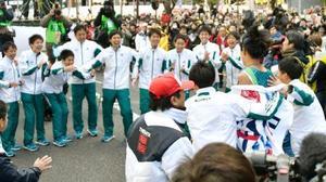 1位でゴールしたアンカー・橋間(手前右から2人目)を迎える青学大のチームメート。奥左端から4人目は原監督=東京・大手町