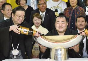 2014年3月、大相撲春場所で初優勝し、祝勝会で大杯を手に笑顔の大関鶴竜。左は井筒親方=大阪市天王寺区