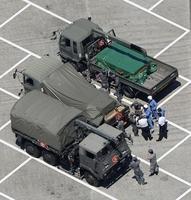 栃木県壬生町の壬生パーキングエリアで自衛隊車両の周辺に集まる自衛隊員ら=6月13日午後1時5分(共同通信社ヘリから)