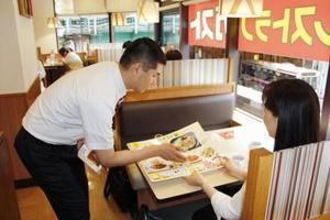 「ガスト中野駅南口店」でメニューを説明する店長(左)=東京都中野区