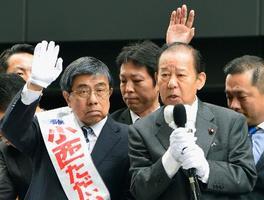大阪府知事選が告示され、支持者に手を振る小西禎一氏。右は応援演説する自民党の二階幹事長=21日午前、大阪市