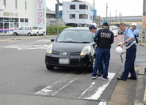児童に衝突した車を調べる警察官=6月11日午前8時25分ごろ、福井県福井市長本町