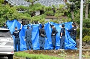 事件が起きた住宅を調べるため、庭などをブルーシートで覆う捜査員=9月11日午前10時ごろ、福井県福井市