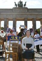 14日、ベルリンのブランデンブルク門前に展示された少女像(共同)