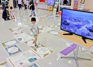 中部縦貫自動車道や下道を模した巨大すごろくを楽しむ子ども=9月26日、福井県福井市のベル
