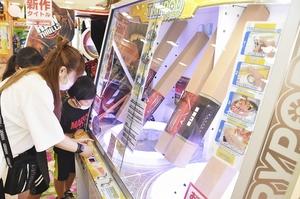 保護者とゲームを楽しむ小学生たち=8月5日、福井市大和田2丁目のゲームセンター「レッツワクワク」