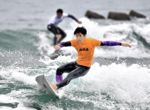 豪快に波に乗るサーファー=27日、福井県あわら市の波松海岸