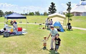 芝生広場でデイキャンプを楽しむ家族連れら=福井県坂井市のゆりの里公園