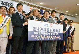 大阪市と吉本興業の包括連携協定締結式に出席した(右4人目から)吉村洋文市長、桂文枝さんら=22日午前、大阪市役所