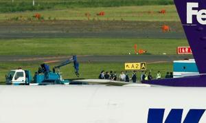 不発弾らしきものが発見された現場周辺を調べる関係者=13日午前7時46分、成田空港