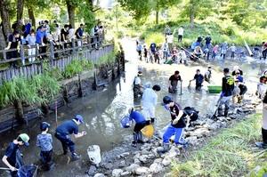 水が抜かれた殿様清水で清掃活動を行う参加者=9月15日、福井県大野市右近次郎