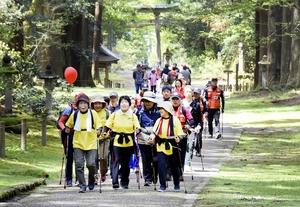 ポールを手に、新緑の平泉寺白山神社境内を歩く参加者=4月28日、福井県勝山市