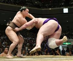 白鵬(左)がすくい投げで栃ノ心を下す=両国国技館