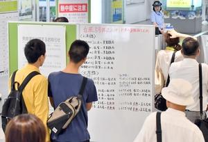 列車運行の掲示板を見る人たち=7日、福井市のJR福井駅