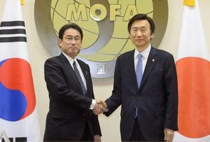 会談を前に韓国の尹炳世外相(右)と握手する岸田外相=28日、ソウルの韓国外務省(共同)